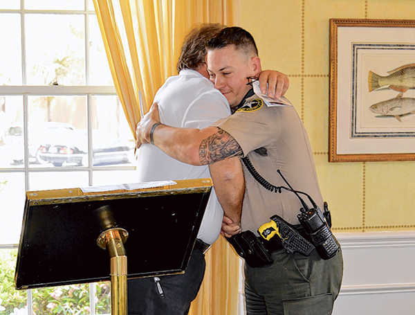Cpl. Stuart Mankin, a Beaufort County sheriff's deputy who is recovering from cancer, hugs Bert DeFazio, president of the Low Country Law Enforcement Officers Association, after receiving a donation from the group to help cover his medical bills. PHOTO SU