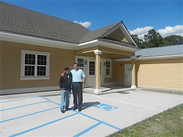 Church member Miguel Monzon, left, and Pastor Israel Mora are pictured in front of the new Seventh-day Adventist sanctuary in Bluffton, which is almost complete. PHOTO BY CAROL WEIR