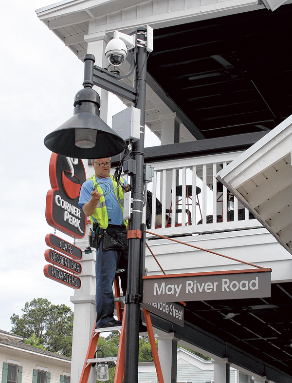 Aworker installs a security camera atop a lightpost outside Corner Perk on May River Road. PHOTO BY B.J. FRAZIER