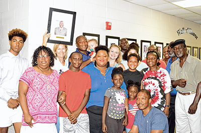 The family of the late Oscar Frazier gathers around Mayor Lisa Sulka, holding his portrait, during his Wall of Honor induction July 12 at Town Hall.