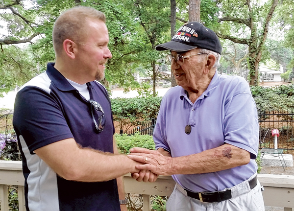 With a firm handshake, Michael J. Piscitello, right, thanks Jeremy E. Shiok for returning his dog tag, now around his neck, that was lost on the South Pacific island of Wallis during World War II. PHOTO BY GWYNETH J. SAUNDERS