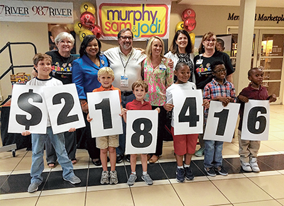 Children helped reveal the total amount raised at the end of the two-day radiothon for the Dwaine & Cynthia Willett Children's Hospital of Savannah. Behind them, from left, are Sue Brown, ReMax Savannah; Dawn Baker, WTOC; Mark Robertson, 98.7 The River;