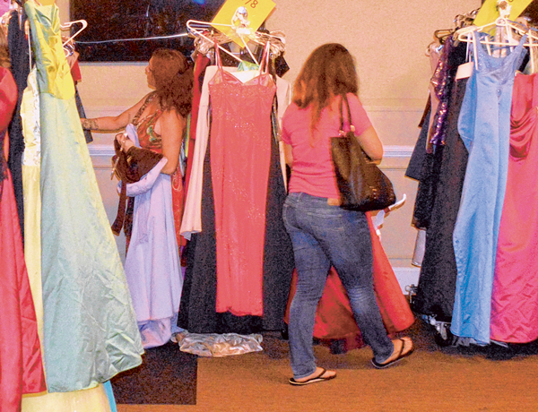 Two recipients in the Operation Ball Gown project peruse the racks for the perfect dress for the Marine Corps Birthday Ball. PHOTO COURTESY MARINE CORPS COMMUNITY SERVICES