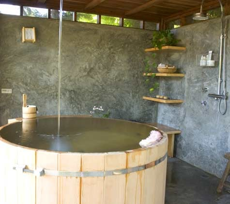 Outdoor Bathroom with Wood Tub, Overhead Spout and Concrete Walls and Floor
