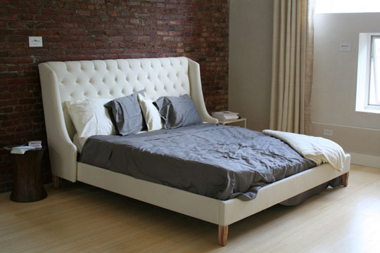White Tufted Bed Against a Brick Wall