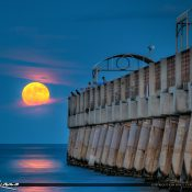 Beautiful moon full moon rising with the Harvest Moon Over the Lake Worth Beach Fishing Pier. HDR image created in Photomatix and processed using Aurora HDR software.
