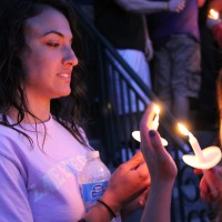 A student lights her candle.