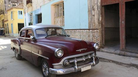 Carro em frente a prédio de Havana