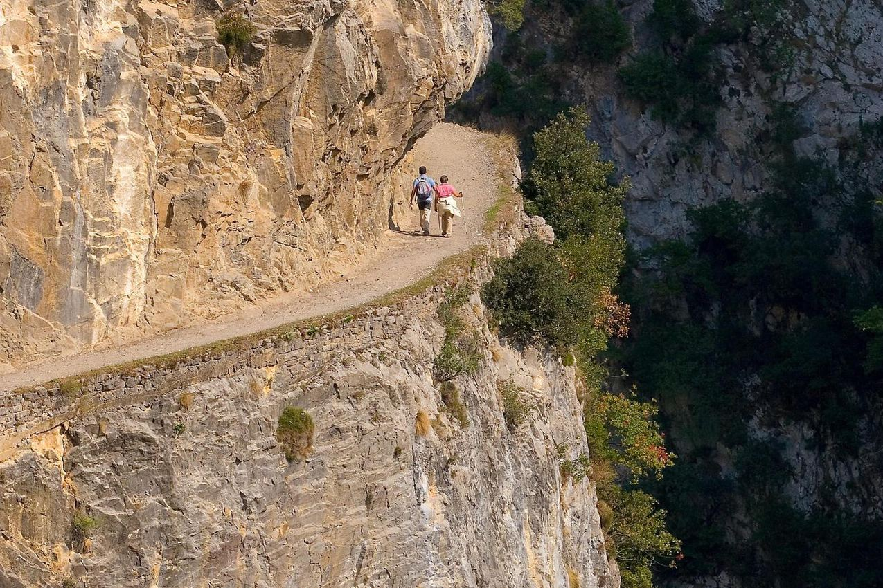spain-picos-de-europa-cares-gorge-two-people-walking-round-corner