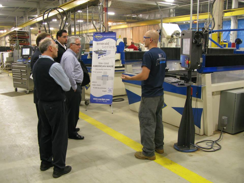 Ken explains the advantages of the low cost Emerald Series waterjet to open house guests