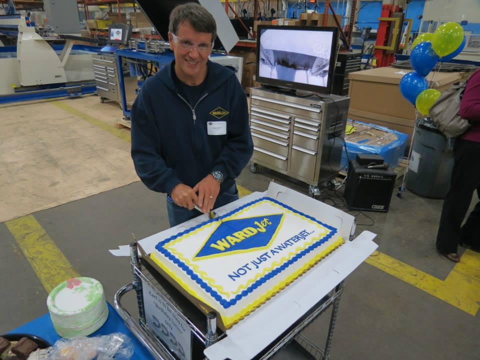Richard Ward cuts the cake to celebrate the first day of the WARDJet open house