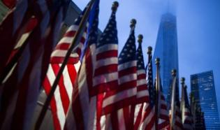 One World Trade Center is seen behind U.S flags on the morning of the 14th anniversary of the 9/11 attacks, in Lower Manhattan i