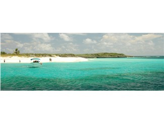 The last Pelican Cay with beautiful deep azure water running along the white sand beach.