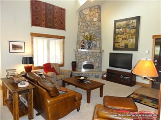Living room with vaulted ceiling, massive rock fireplace and flatscreen TV.
