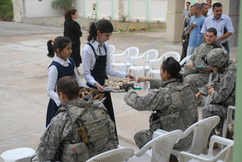 Capt. Patrick Soule and 1st Lt. Rosita Rodriguez enjoy refreshments handed out by a student at the opening of Al Tajadud elementary school Oct. 26 in the Adhmaiyah District of Baghdad.