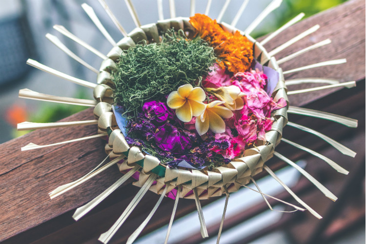 canang sari, colored flowers in coconut leaf basket