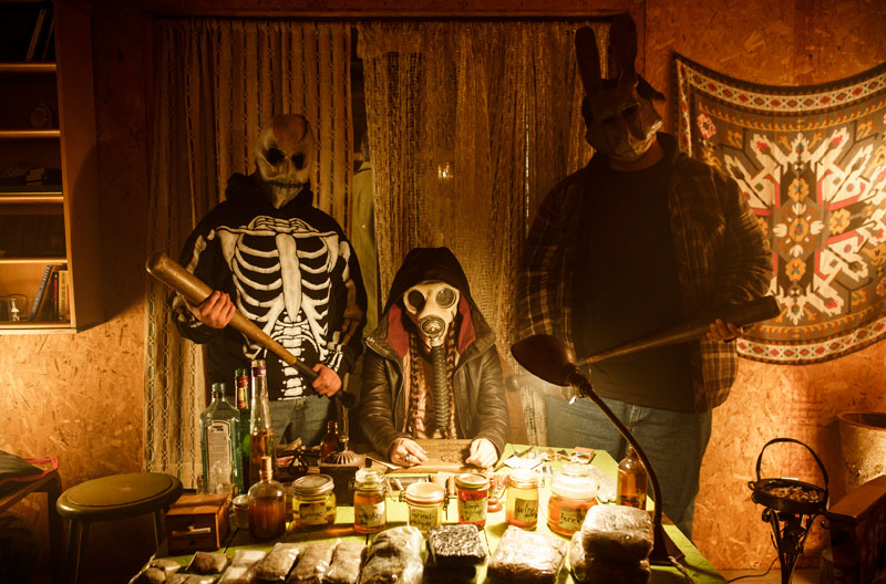 Three people wearing masks sit at a table to organize marijuana.