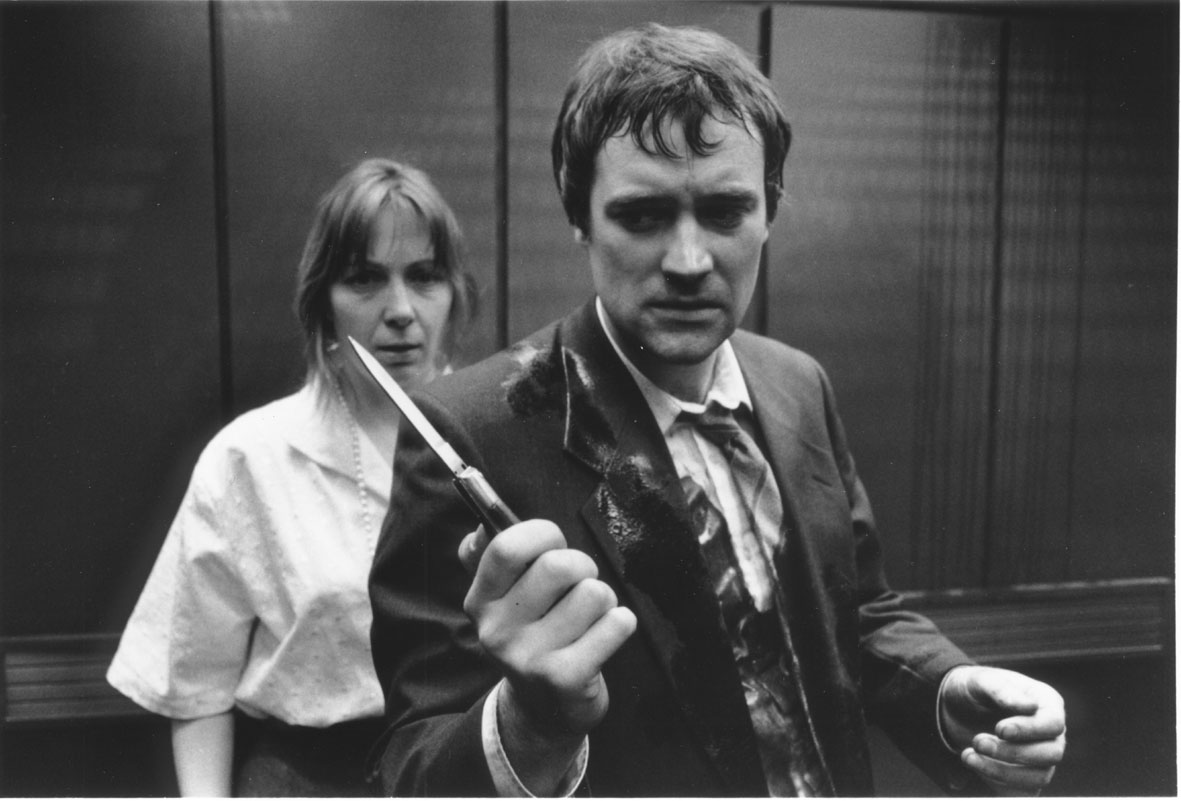 A man, holding a knife, stands in an elevator with his back to a woman