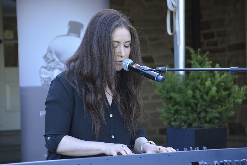 Singer performing and playing piano at CFC Garden Party