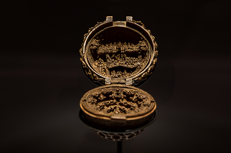 A close-up of the gothic boxwood miniature prayer bead, which depicts heaven and hell.
