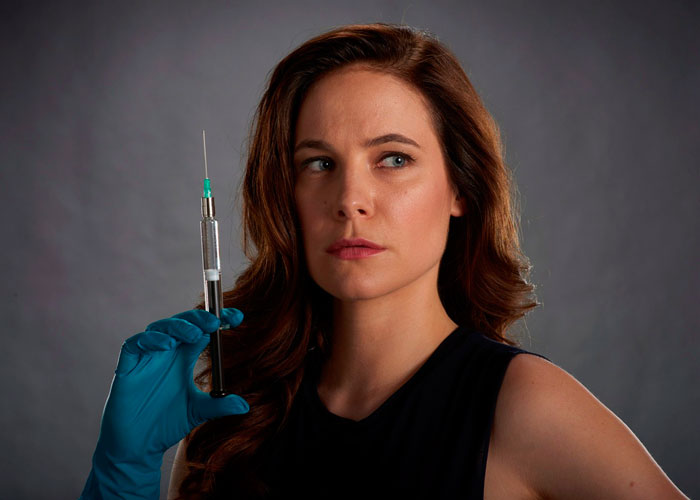 A woman wears a rubber glove and holds a needle