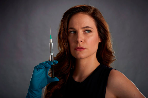A woman holding a syringe.