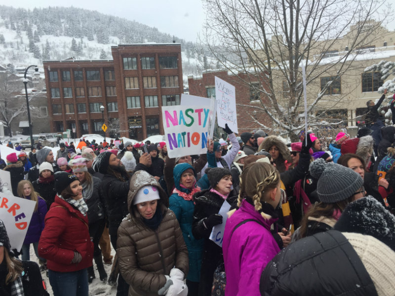 A crowd of women outside gathering to march