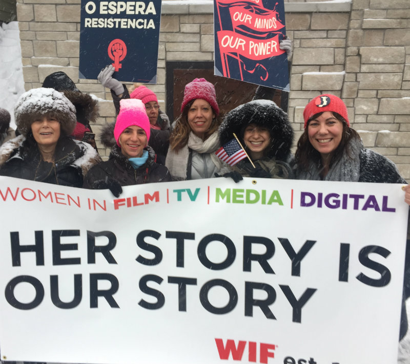 Women holding up banner that reads her story is our story