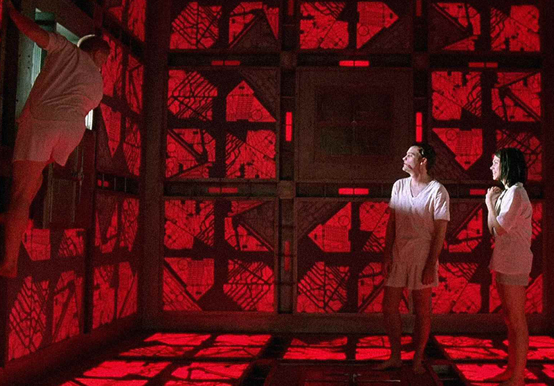Two people watch a man climb the walls in a red and black, cube-shaped room.