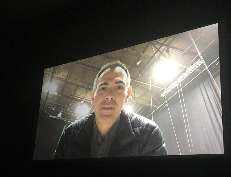 Man speaking a pre-recorded message on a movie screen.