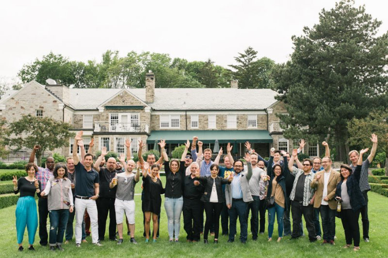 cohort 6 companies standing with hands in the air