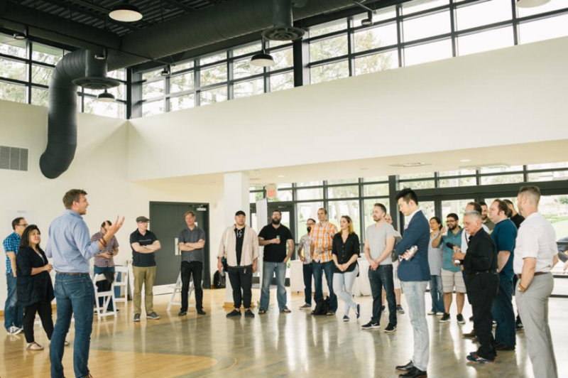 Man addressing a group standing in a big circle