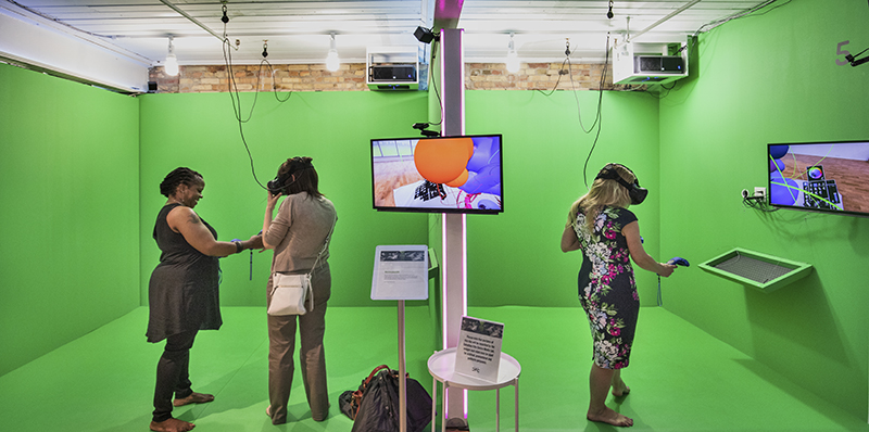 Three people in a green screen room experiencing Virtual Reality (VR).