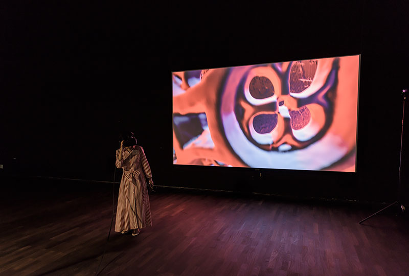 Woman standing and wearing a VR headset, with an abstract design on a screen projected behind her.