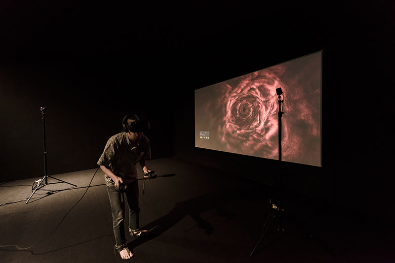 Man wearing a VR headset standing and leaning forward, with an abstract design on a screen projected behind him, and two standing microphones on either side.