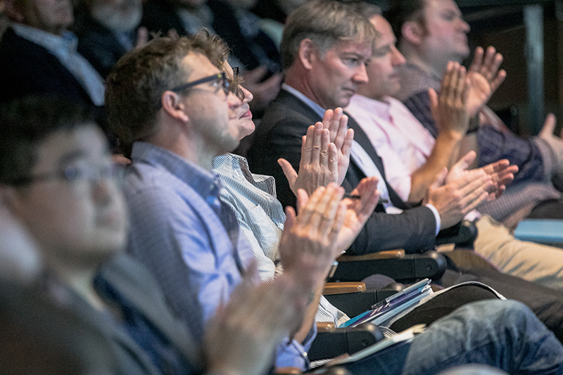 Members of an audience applauding.