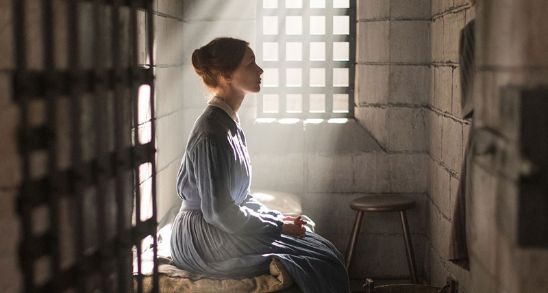 Side profile of a woman sitting in a cell, with sun shining in from the window.