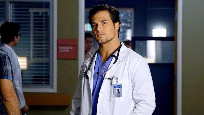 An actor playing a doctor standing in a hospital hallway with a stethoscope around his neck