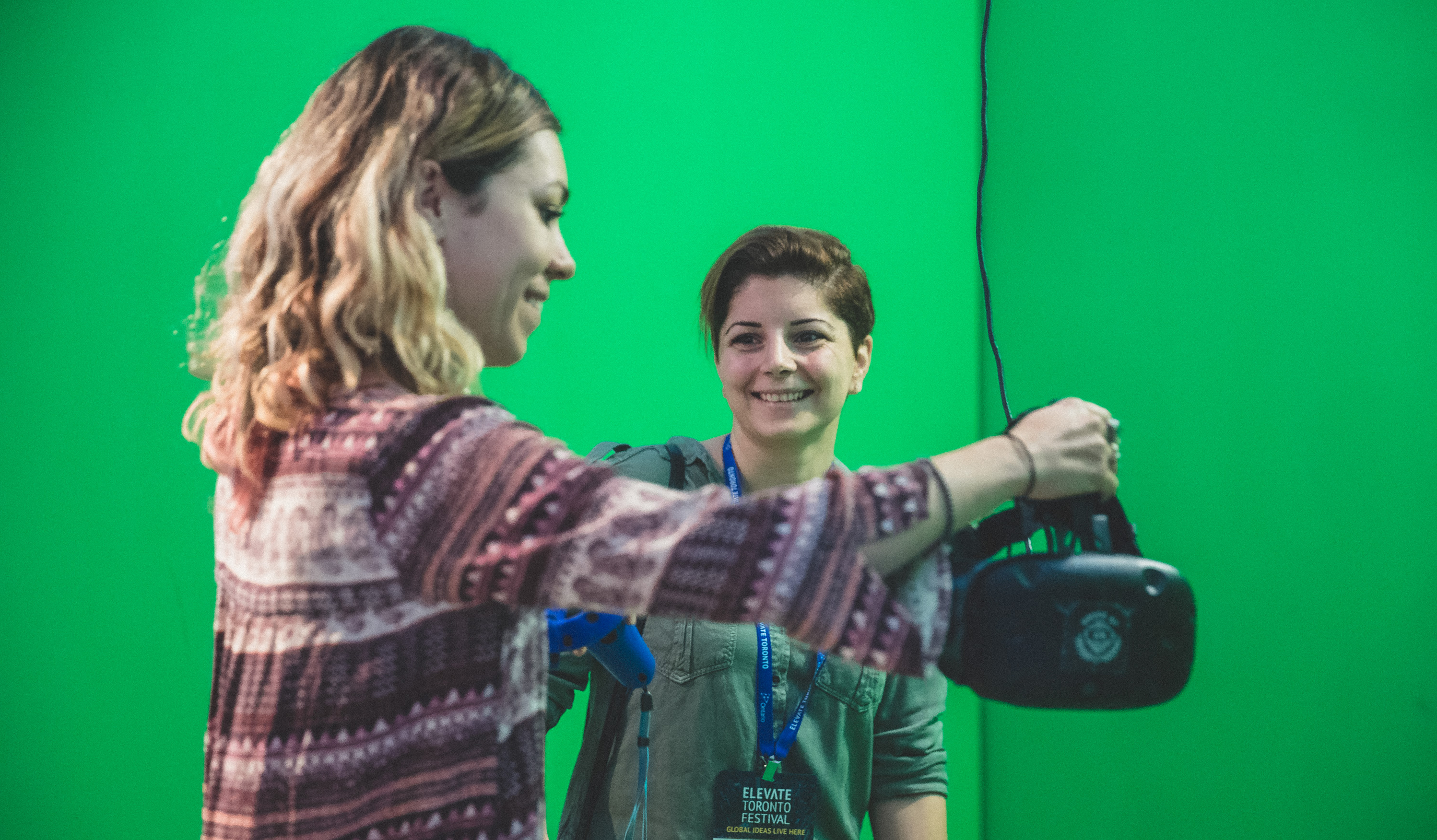 Two women using a headset in a mixed-reality green screen playstation.