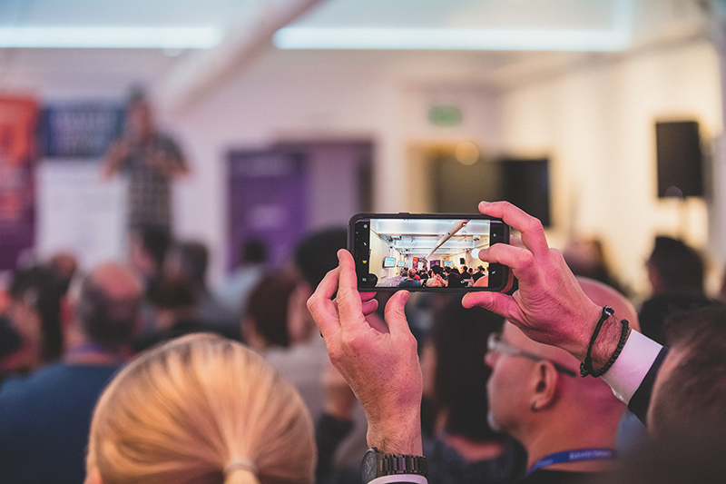 Man taking a cell phone photo of a speaker and audience, blurry in background.