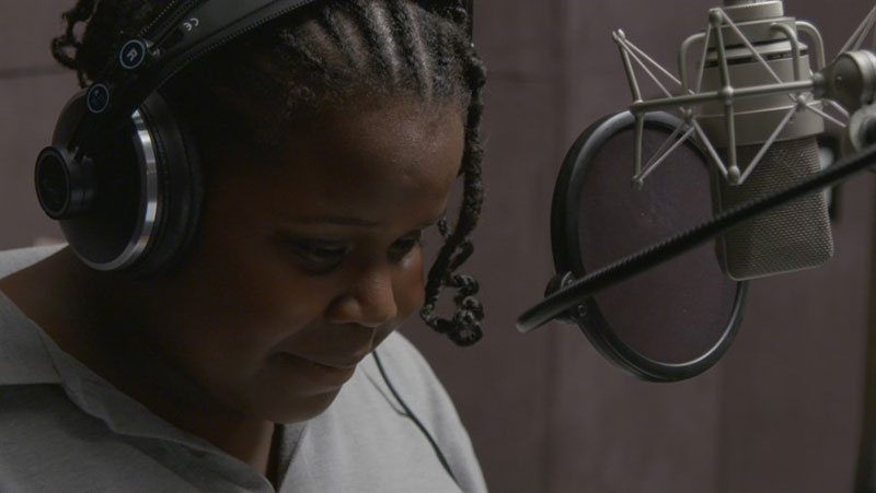 A young woman wearing headphones in a recording booth