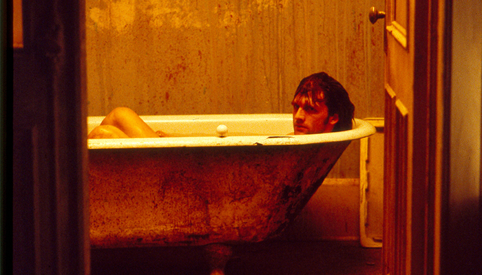 A man lies in a bloody bathtub