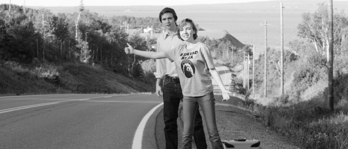 Two people hitchhiking by the side of the road.