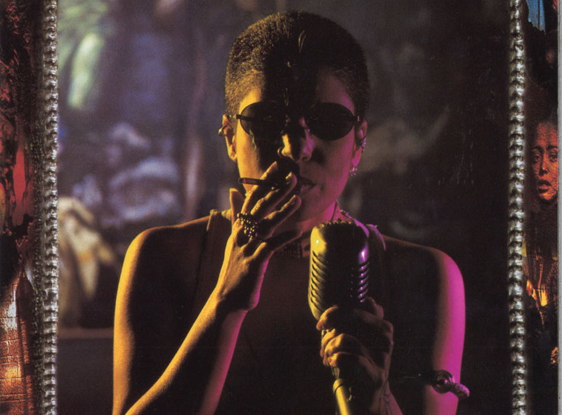 A woman smokes a cigarette and holds a microphone while wearing sunglasses