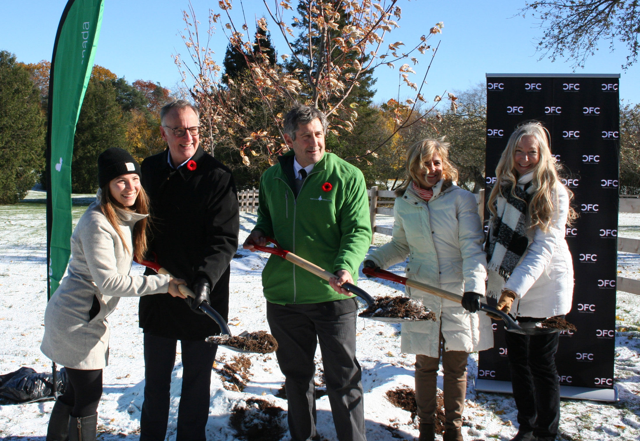 Five people holding shovels outside in front of a tree at a tree planting ceremony