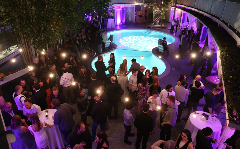 Guests mingle with cocktails around a pool in the evening.