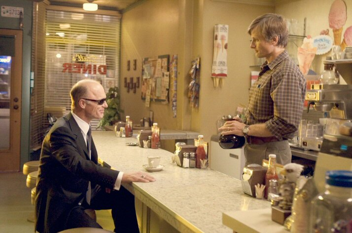 A man standing behind a counter serves coffee to another man sitting at a counter.