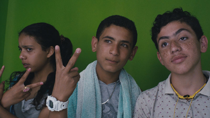 Three youths make peace signs with their hands for a picture.