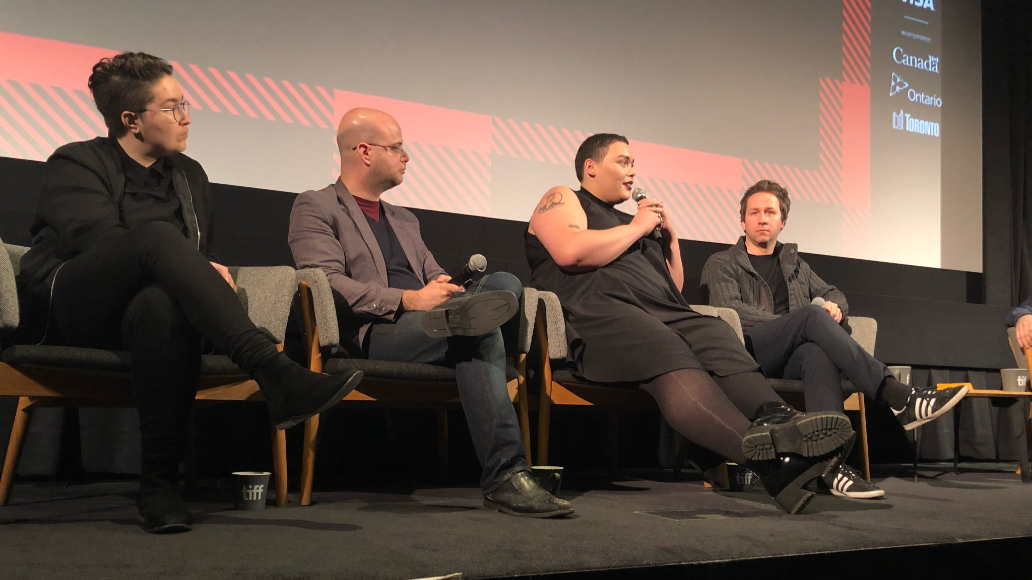 Four individuals sit on a stage as part of a panel.