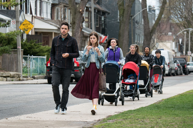 A group of people walking on the sidewalk with strollers